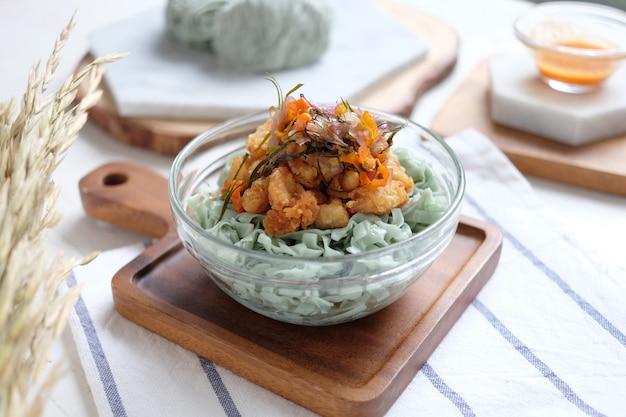 Nouilles vertes non cuites avec viande et pépite de poulet sur le bol Photo Premium