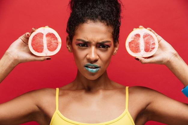 La Nourriture Afro-américaine Fronçant Les Sourcils Avec Le Maquillage à La Mode Tenant Deux Moitiés De Pamplemousse Mûr Frais Dans Les Deux Mains Isolées, Sur Le Mur Rouge Photo gratuit