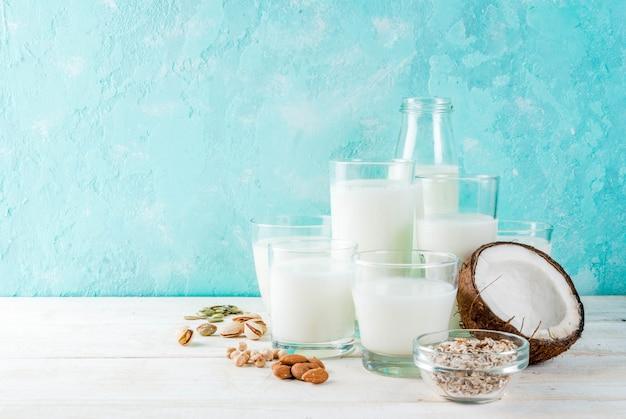 Nourriture alternative végétalienne, assortiment de divers produits laitiers non laitiers - riz, noix de coco, amandes, pistaches, sésame, graines de citrouille, soja, noix, farine d'avoine Photo Premium