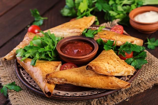 Nourriture asiatique. samsa (samosas) avec filet de poulet et fromage sur bois. Photo Premium