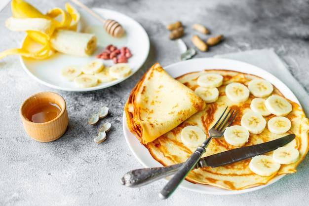 Nourriture, dessert, pâtisseries, crêpes, tarte. délicieuses crêpes à la banane et au miel sur un fond de béton Photo Premium