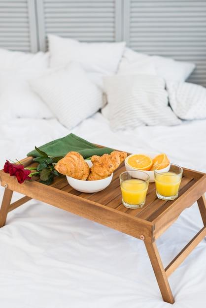Nourriture et fleurs sur la table du petit déjeuner sur le lit Photo gratuit