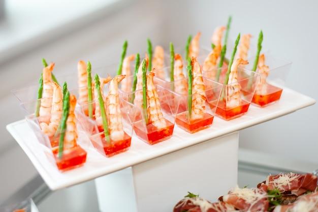 Nourriture lors de l'événement: gobelets en plastique jetables avec collations, crevettes aux asperges et sauce aigre-douce. Photo Premium