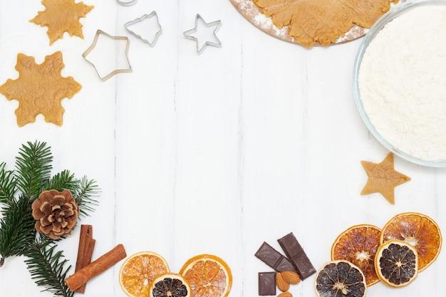 Nourriture De Noël. Copyspace. Biscuits De Pain D'épice Faits Maison Avec Des Ingrédients Pour La Cuisson De Noël Et Des Ustensiles De Cuisine Sur Un Tableau Blanc Photo Premium