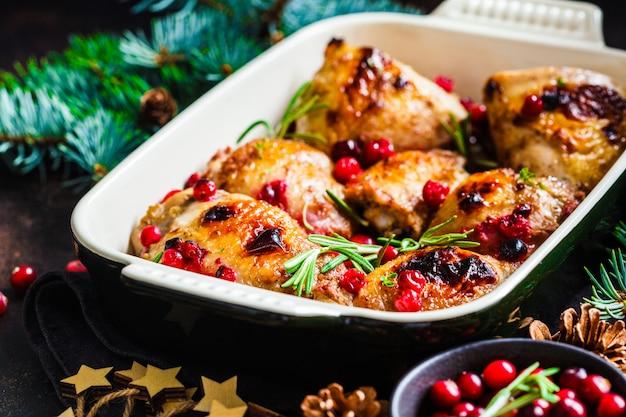 Nourriture de noël, viande de poulet au four avec canneberges et romarin dans le plat du four Photo Premium