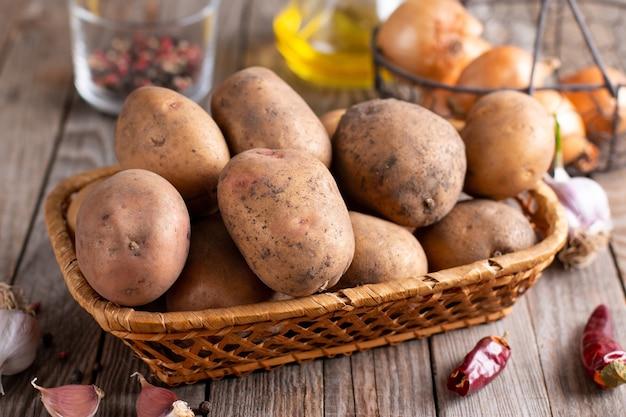 Nourriture De Pomme De Terre Crue. Pommes De Terre Fraîches Sur Fond De Bois Photo Premium