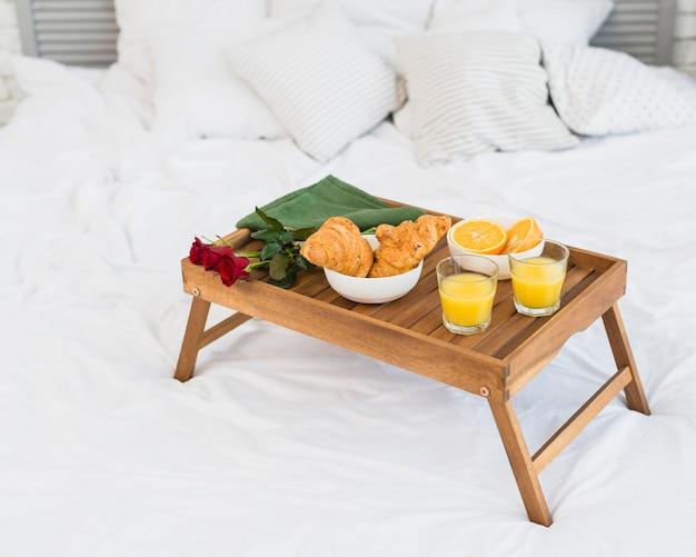 Nourriture et roses sur la table du petit déjeuner sur le lit Photo gratuit