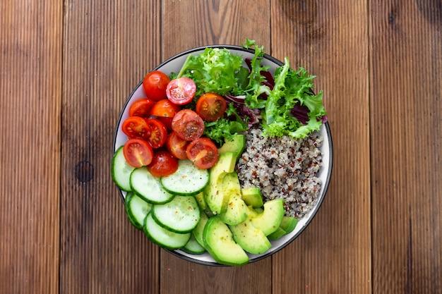 Nourriture saine. bol budha avec quinoa, avocat, concombre, salade, tomate, huile d'olive. Photo Premium