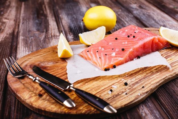 Nourriture saine et fraîche. saumon cru servi avec des citrons et des couteaux sur une planche de bois Photo gratuit