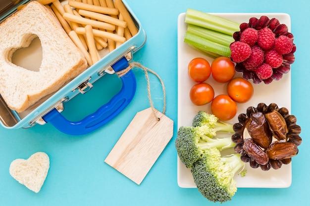 Nourriture saine près de la boîte à lunch étiquetée Photo gratuit
