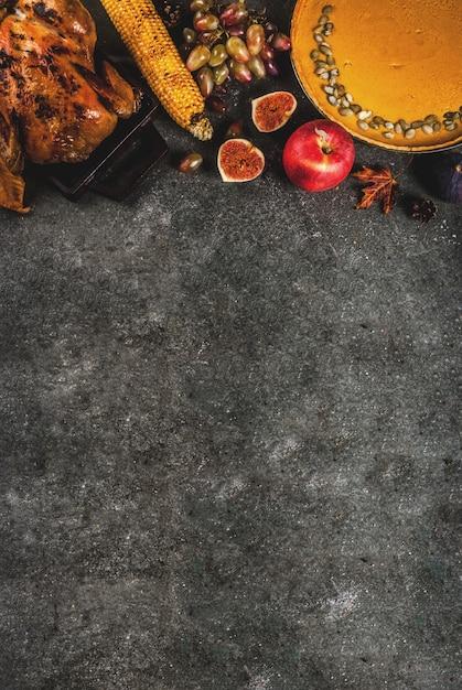 Nourriture De Thanksgiving Day. Poulet Entier Ou Dinde Rôti Aux Fruits Et Légumes D'automne: Maïs, Citrouille, Tarte à La Citrouille, Figues, Pommes, Sur Gris Foncé, Vue De Dessus Photo Premium