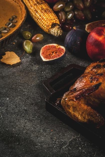 Nourriture De Thanksgiving Day. Poulet Entier Ou Dinde Rôti Aux Fruits Et Légumes D'automne: Maïs, Citrouille, Tarte à La Citrouille, Figues, Pommes, Sur Gris Foncé, Photo Premium