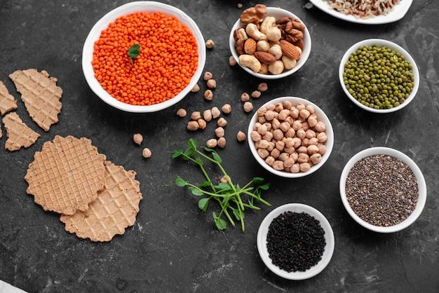 Nourriture végétalienne saine sur un fond de béton avec espace de copie. noix, haricots, légumes verts et graines Photo Premium