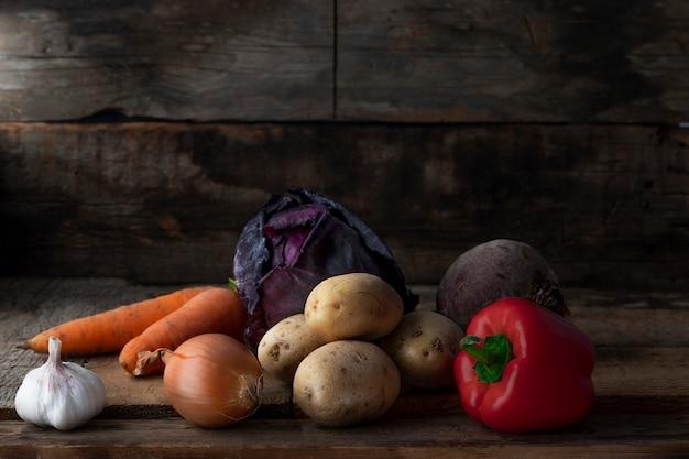 Nourriture végétarienne crue. légumes frais dans un sellar sur fond en bois. Photo Premium