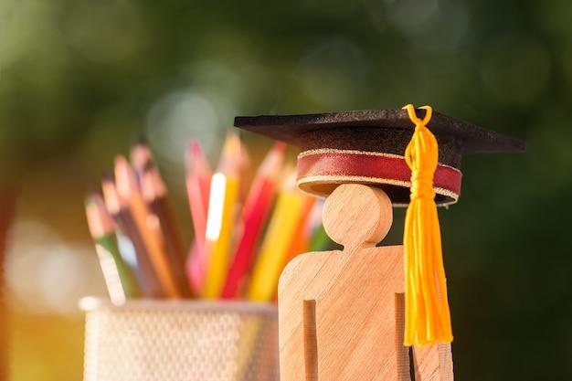 De nouveau au concept de l'école, les gens signent du bois avec la boîte à crayons flou chapeau graduation célébrant. Photo Premium