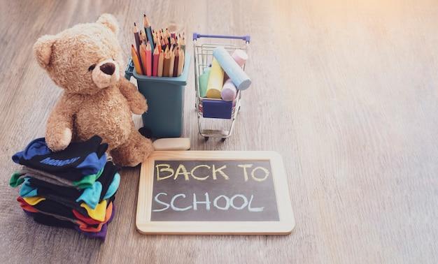 De nouveau au fond d'école avec le tableau ardoise, des crayons, des craies Photo Premium
