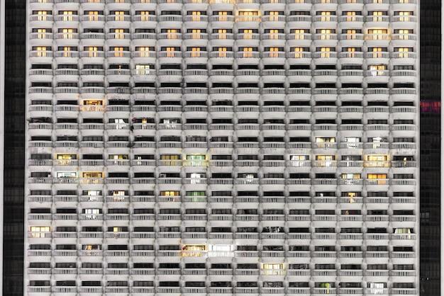 Nouveau bloc d'appartements modernes ou condominium avec balcon dans la nuit Photo Premium