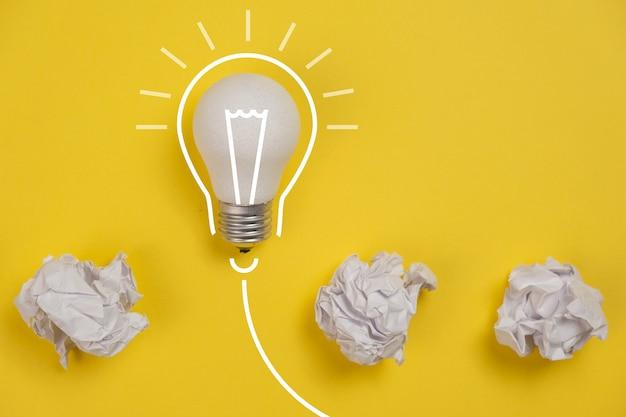 Nouveau Concept D'idée Avec Du Papier De Bureau Froissé Et Une Ampoule Blanche Sur Fond Jaune. Solution Créative Lors Du Concept De Session De Remue-méninges. Mise à Plat, Vue De Dessus, Espace Copie Photo Premium