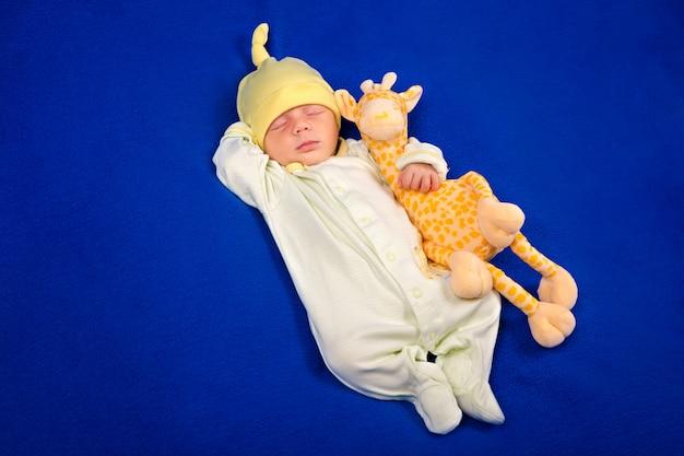 Nouveau-né Couché Sur Une Couverture Bleue Avec Girafe Jouet. Garçon Ou Fille Photo Premium
