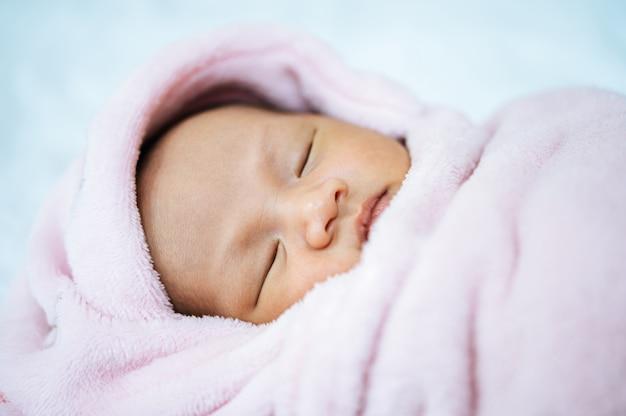 Nouveau-né dort sur une couverture rose tendre Photo gratuit