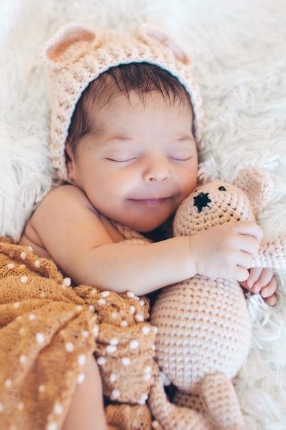 Nouveau-né dort avec un jouet à côté de l'ours en peluche Photo Premium
