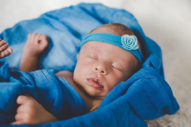 Nouveau-né Endormi Sur Un Fond Bleu. Mise Au Point Sélective. Gens. Photo Premium