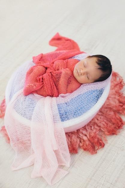 Nouveau-né enveloppé dans une couverture dormant dans un panier. concept d'enfance, de santé, de fiv Photo Premium