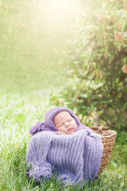Un nouveau-né souriant de 17 jours dort sur le ventre dans le panier sur la nature dans le jardin en plein air. Photo Premium