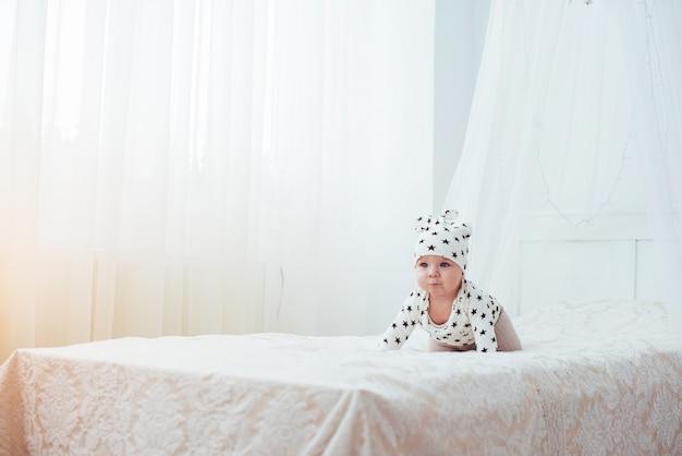 Un nouveau-né vêtu d'un costume blanc et d'étoiles noires est un lit moelleux blanc Photo Premium