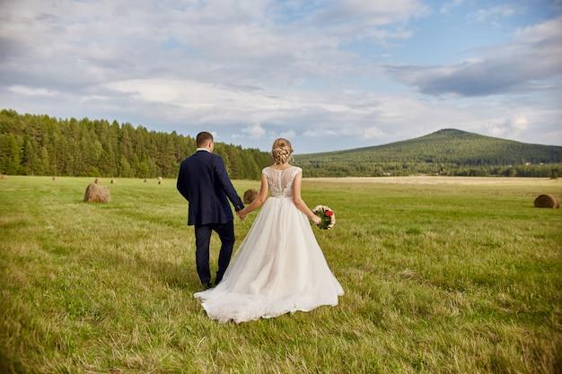 Les nouveaux mariés marchent et se détendent dans le champ Photo Premium