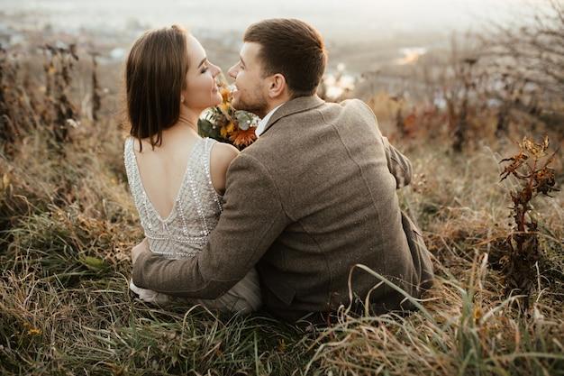 Les nouveaux mariés se réjouissent l'un l'autre sur la montagne Photo gratuit