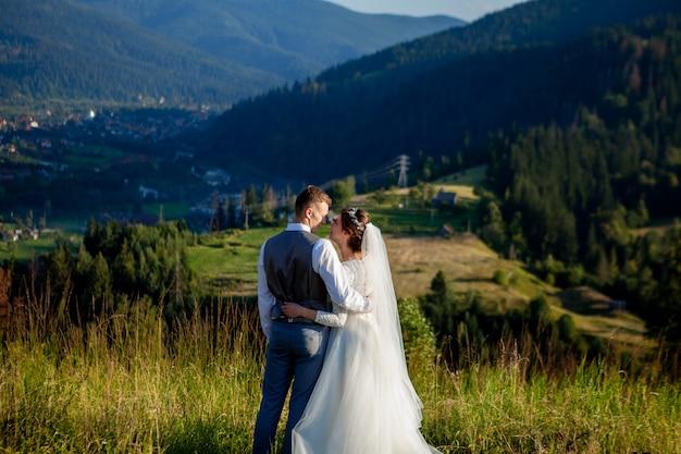Les Nouveaux Mariés Se Sourient Et S'embrassent Dans La Prairie Au Sommet De La Montagne Photo Premium