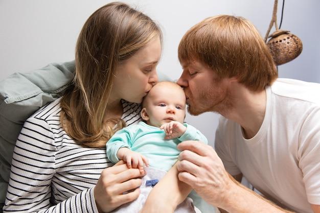 Nouveaux Parents Embrassant La Tête De Bébé Aux Cheveux Rouges Photo gratuit