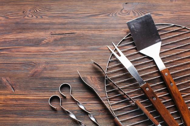 Nouveaux ustensiles de barbecue métalliques sur fond en bois Photo gratuit