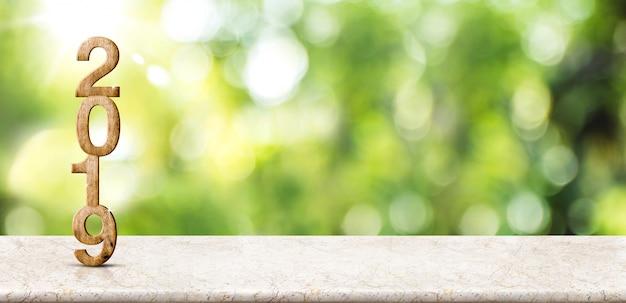 Nouvel an 2019 sur une table en marbre au flou bokeh vert abstrait avec fond de rayon de soleil Photo Premium