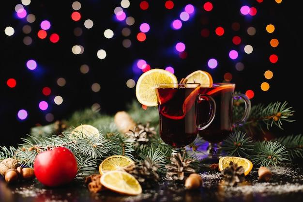 Nouvel an et décor de noël. verres à vin chaud debout sur une table avec des oranges Photo gratuit