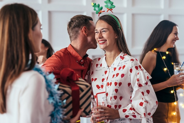Nouvel An, Noël, L'homme Dit Quelque Chose à L'oreille De Sa Copine Ou L'embrasse Dans La Joue Photo Premium
