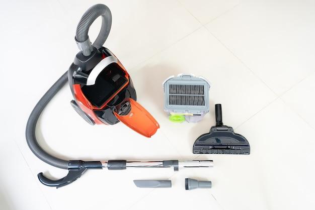 Nouvel aspirateur et nettoyeur de têtes de brosse sur un sol en carrelage blanc Photo Premium