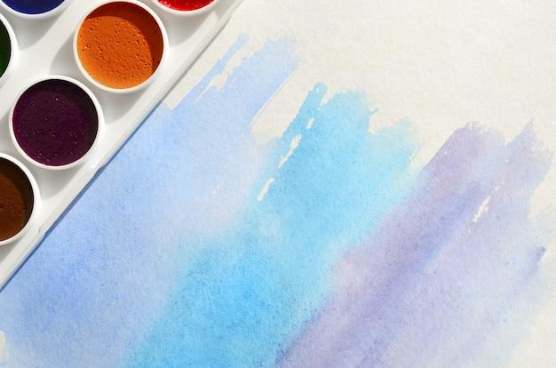 Un nouvel ensemble d'aquarelles repose sur une feuille de papier, qui montre un dessin à l'aquarelle abstrait sous la forme de traits bleus. Photo Premium