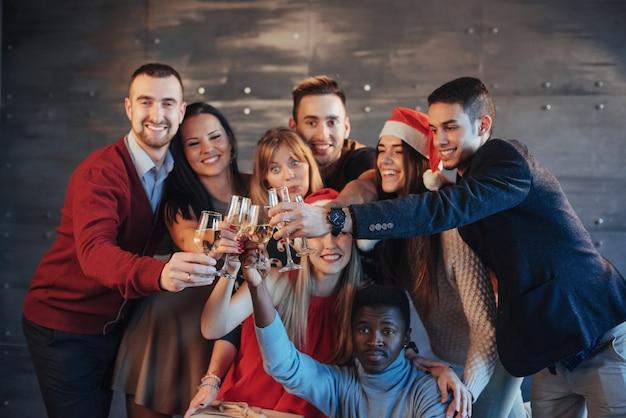 La nouvelle année arrive! groupe de joyeux jeunes multiethniques en chapeaux santa sur la fête, posant le concept de peuple lifestyle émotionnel Photo Premium