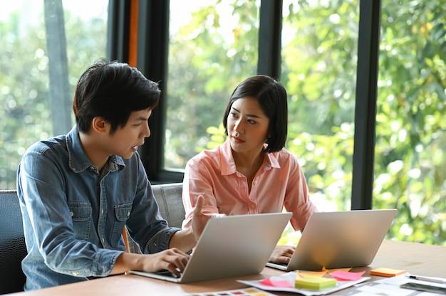 La nouvelle génération de jeunes hommes et femmes est assise, consulte, travaille et utilise un ordinateur portable sur son bureau. Photo Premium