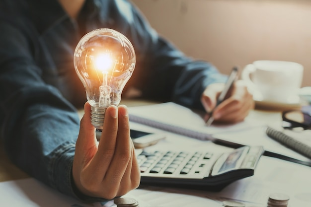 Nouvelle idée et concept créatif pour femme d'affaires main tenant l'ampoule au bureau Photo Premium