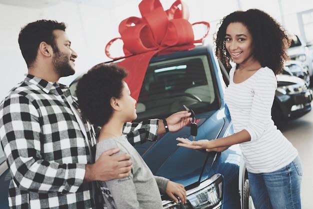 Une nouvelle voiture avec un homme avec un arc rouge donne les clés à une femme Photo Premium