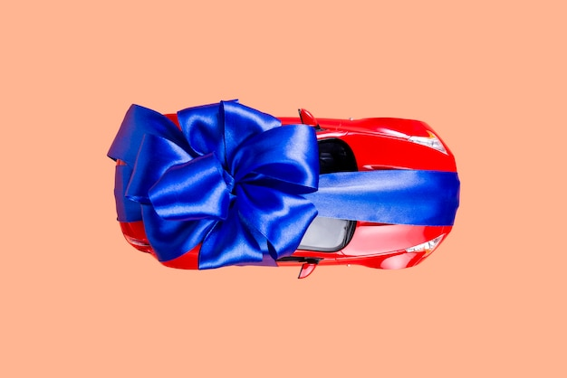 Nouvelle voiture rouge avec un arc bleu en cadeau sur du corail Photo Premium
