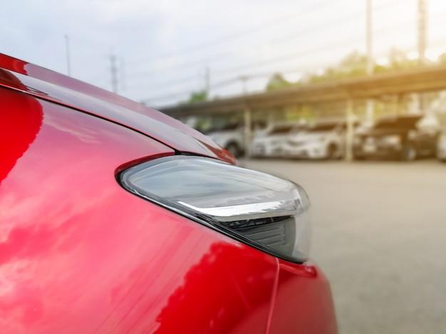 Nouvelle voiture rouge dans le parc avec beaucoup de voitures sur le parking Photo Premium