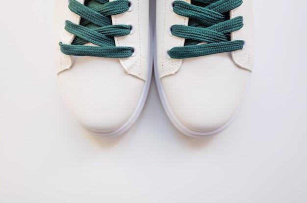 Nouvelles baskets blanches à lacets verts sur fond blanc Photo Premium