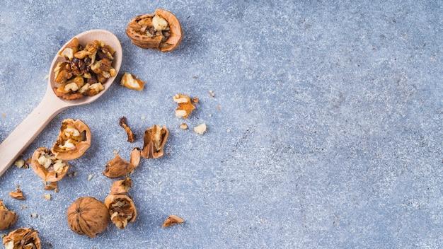 Noyau de noix sur une cuillère en bois sur le fond de granit Photo gratuit