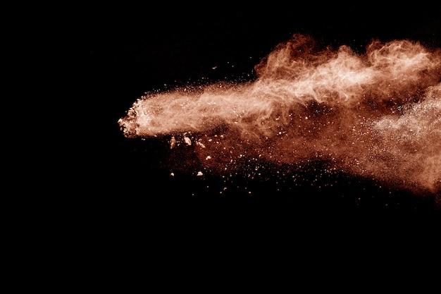 Nuage d'explosion de poussière brune. éclaboussures de particules marron sur fond noir. Photo Premium