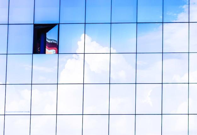 Nuages Reflétés Dans Les Fenêtres De L'immeuble De Bureaux Moderne De Gratte-ciel. Avec Une Fenêtre Ouverte. Photo Premium