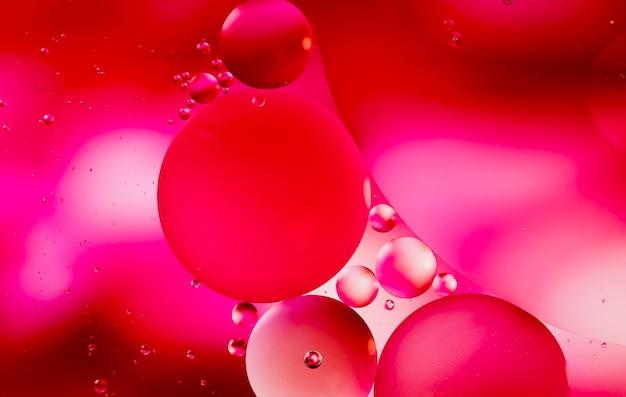 Des nuances rougeâtres d'huile tombe sur un fond abstrait de la surface de l'eau Photo gratuit